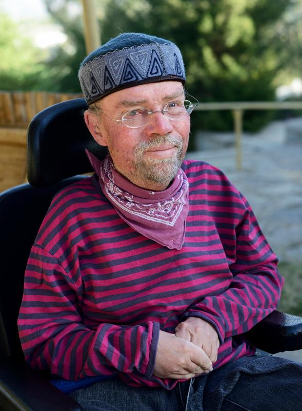 Man seated in powerchair wearing pink-striped shirt and blue hat looks at camera.