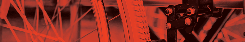 A photo in red and black showing parts of a wheelchair frame and wheels