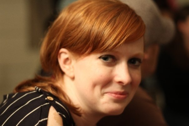 A smiling, redheaded woman looks slightly of her right shoulder at the camera.