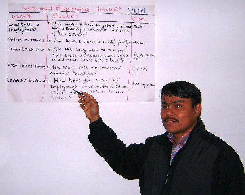 A gentleman in a dark coat points to a paper chart on the wall that discusses the CRPD's Article 27