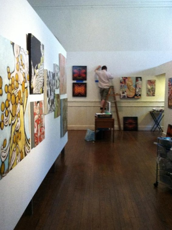 Matthew Saindon installing, Mattye Hamilton's Paintings (left) Cara Bishoff (right)