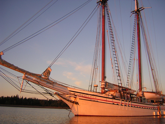 Schooner Heritage at anchor in a warm sunset