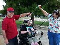Man using wheelchair with adapted fishing rod with his fish, Dad, and friend