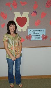 Susan Galindo stands by display on A Servant's Heart, Helping Hands