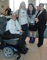 Three female attendees standing next to male attendee seated in a power wheelchair