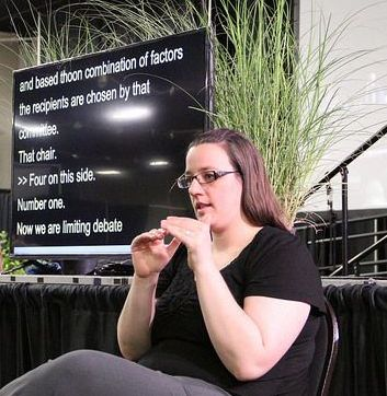Woman signing sits in front of stage near a screen displaying captions