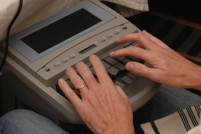 Two hands touch keys of a steno machine with screen
