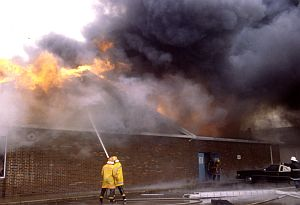 Two firemen work to extinguish a building fire
