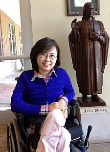 Jinwook Oh seated in wheelchair in front of John Wesley statue
