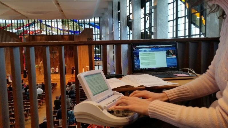 Image shows arms and hands ofa woman using steno machine in the balcony of Lovers Lane church with view of congregants and stained glass windows in the sanctuary below