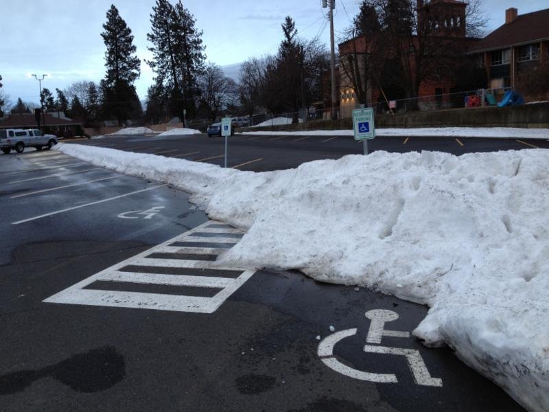 Accessible parking spaces made unusable by piles of snow intentionally piled there by snow plow operators