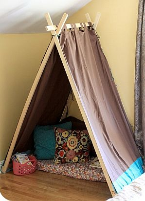 indoor tent made with boards and fabric, pillows inside