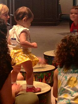 Child walking on drums as others watch