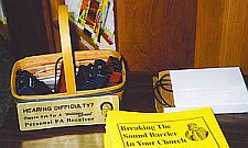 basket containing assistive listening device receivers and a stack of Breaking the Sound Barrier in your Church booklets