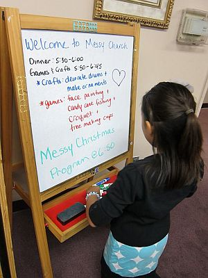 Girl reading a welcome board about Messy Church