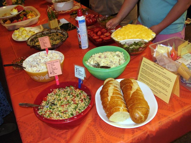 Various potluck foods with lables attached