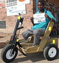 African man with both legs amputed in his new PET wooden hand crank cart