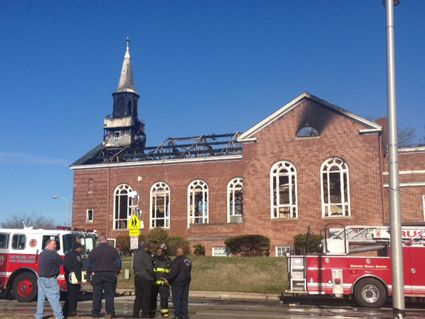 Fire fighters and others stand outside burned church; 2 fire engines are still present