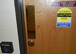 restroom door with signage about automatic door and family use