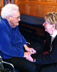 older woman seated in wheelchair holding hands with volunteer kneeling in front of her