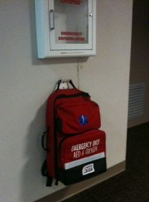 Red backpack containing AED and emergency supplies hangs on wall