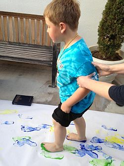 Boy with painted feet walking on butcher paper