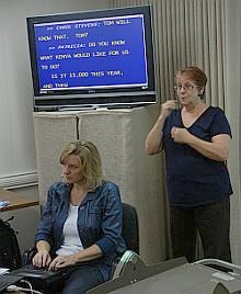 CART provider typing, screen with captions, and ASL interpreter at DHM meeting