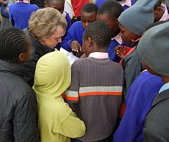 Rev. Ann Adams surrounded by Kaaga students