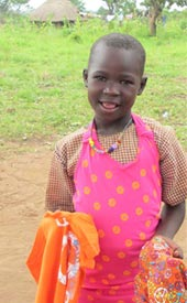 Akello Teddy, a sponsored child from Agwata, shows a gift she received.