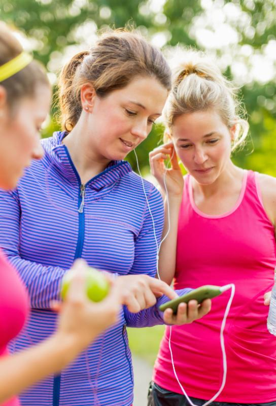 women checking smartphone during exercise
