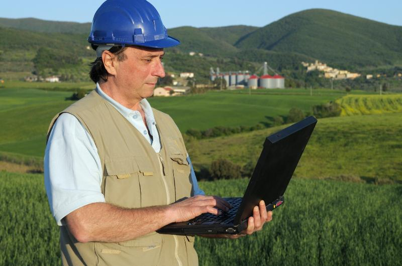Engineer with laptop in rural setting