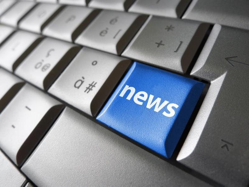 Online news Internet concept with news sign and symbol on a blue laptop computer key for blog website and online business.