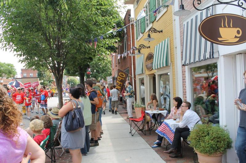 Cafemantic customers watch the Fourth of July parade as they sip their iced coffee in downtown Willimantic.