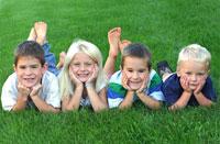 four cute children in the grass