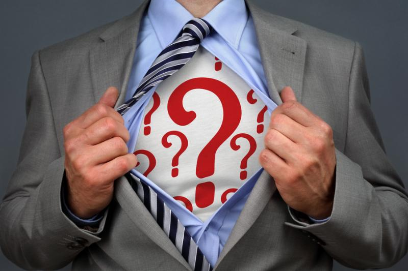 Businessman in classic superman pose tearing his shirt open to reveal question mark symbol on chest concept for human resources and recruitment