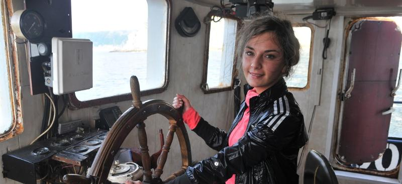 Girl steering the boat wheel