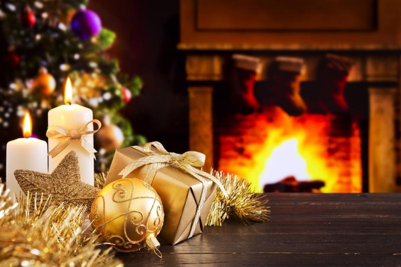 Christmas decorations, a gift and candles in front of a   fireplace. A fire is burning in the fireplace and   Christmas stockings are hanging on the mantelpiece. A   Christmas tree is standing next to the fireplace in the   background.