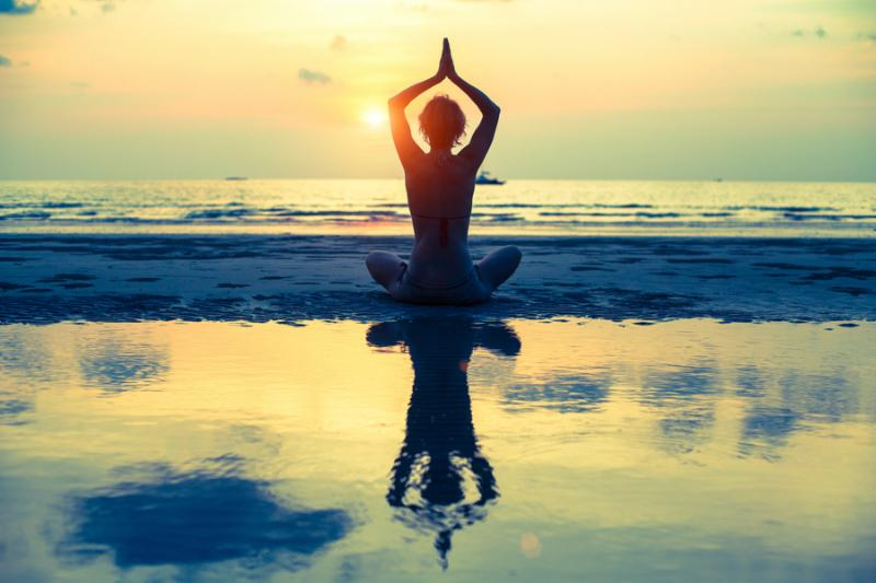 Yoga woman sitting in lotus pose on the beach during sunset, with reflection in water ...