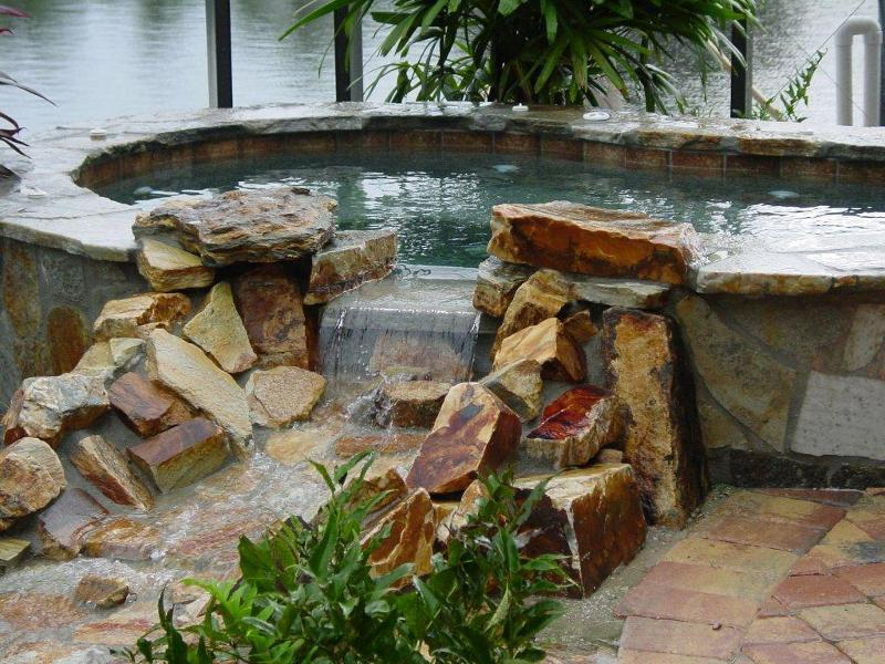 Stone faced raised spa with natural rock brook to pool