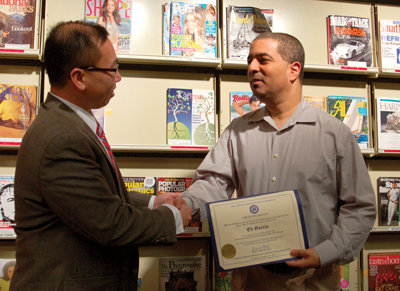 Information Access Librarian Ed Garcia accepts a citation from Cranston Mayor Alan Fung.