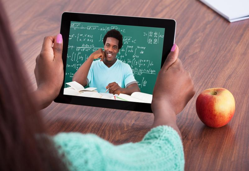 Cropped image of female teacher assisting student through video conferencing at classroom