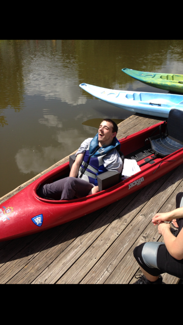 Nick is in a kayak smiling awaiting departure into the water.