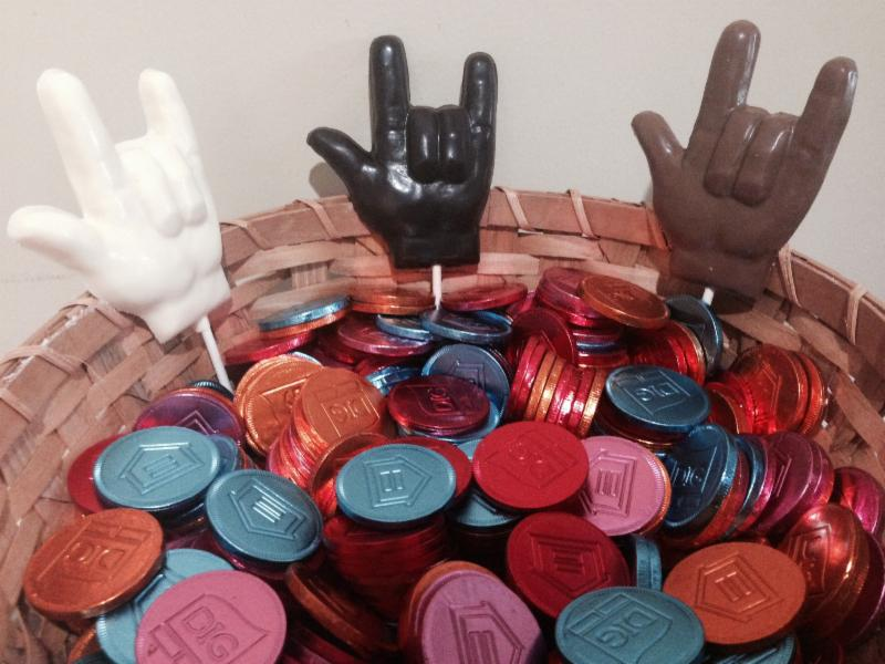 A basket of colored chocolate medallions and 3 chocolate hand that say I love you in ASL.