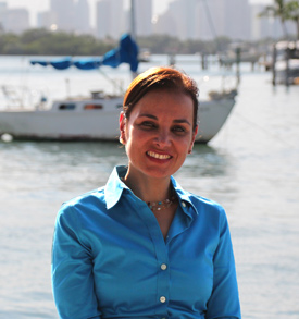 Head shot of Patricia Bochi. She is in front of a boat that is in the water.