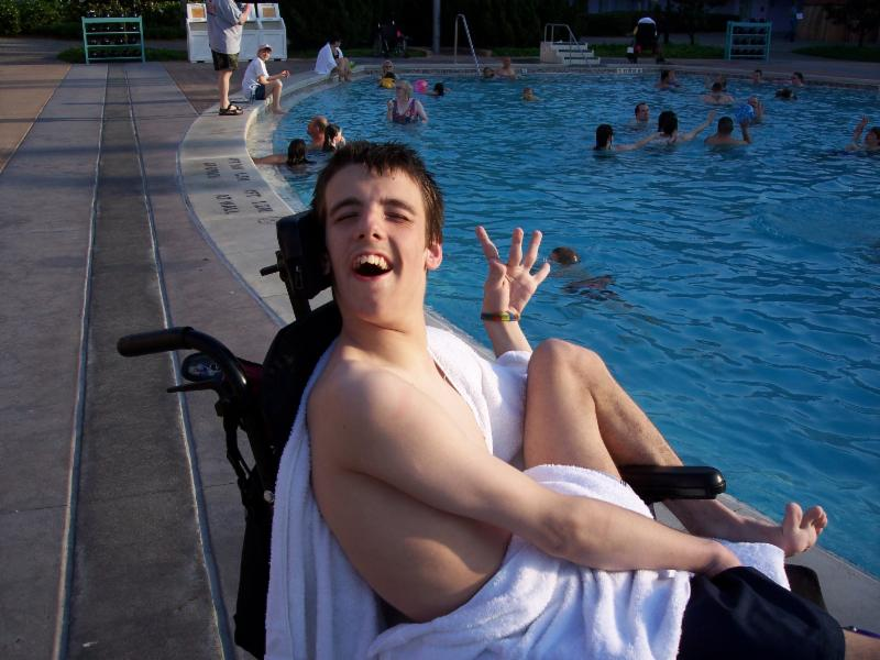Nick smiling in his wheelchair on the side of the pool.