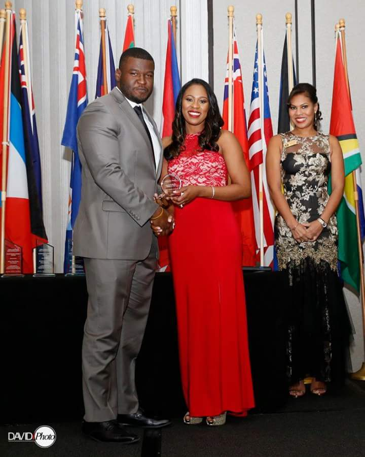 Samuel Rony poses with Esq. Nikisha Pryor and Esq. Sharaine Sibblies while accepting his award