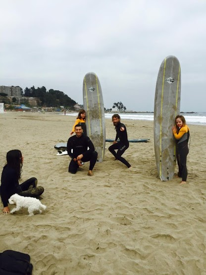 Mick, Pili, Anita, and Olmer posing with surfboards on the beach