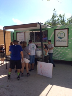 Nature Links Food Truck with students working the truck and customers waiting in line to order food.