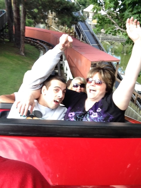 Nick and Julie are on a roller coaster. Both people are smiling with their hands in the air