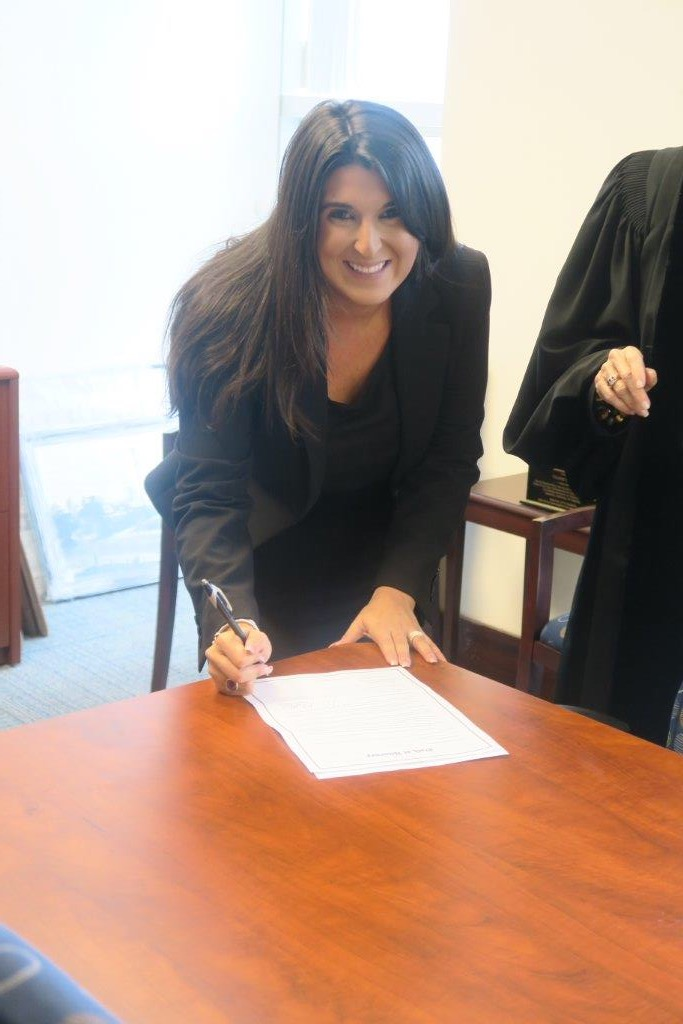 Lisa signing the oath of attorney with Judge Muir.